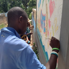 Students and volunteers work together to paint murals outside of New Life School