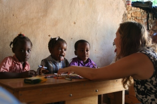 Volunteer, Sarah Letsche, has some fun with students at New Life School